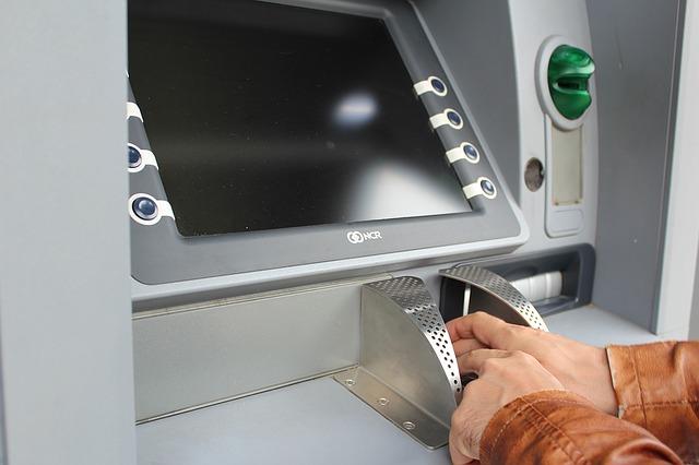 Verdeckte PIN-Eingabe eines Mannes am Geldautomaten