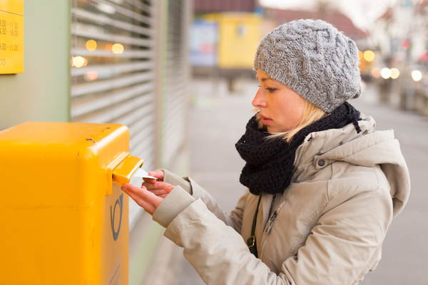 Frau wirft Brief in den Briefkasten