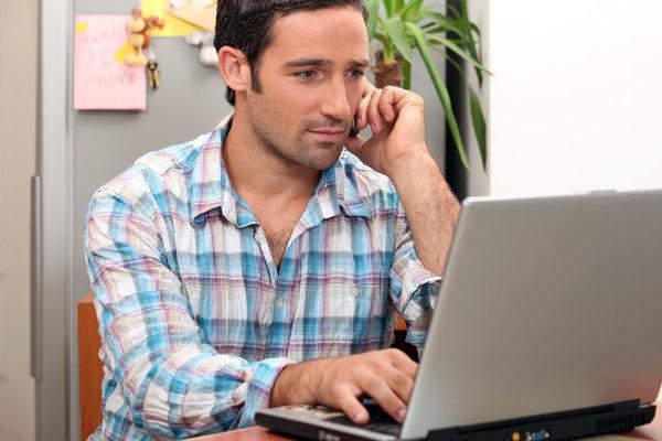 Mann telefoniert am Laptop