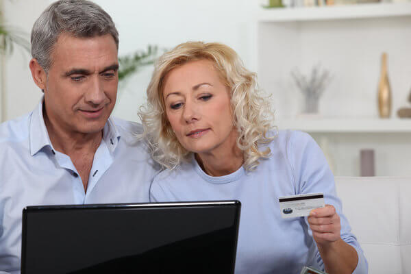 Älteres Ehepaar vor dem Laptop mit Kreditkarte