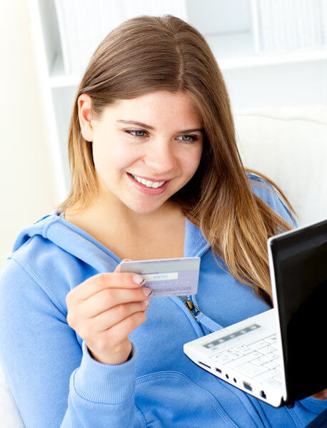 Frau sitzt mit einer Kreditkarte vor dem Laptop