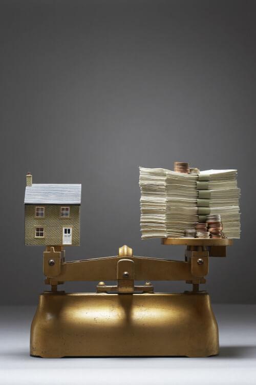 Waage mit Geld und Immobilie