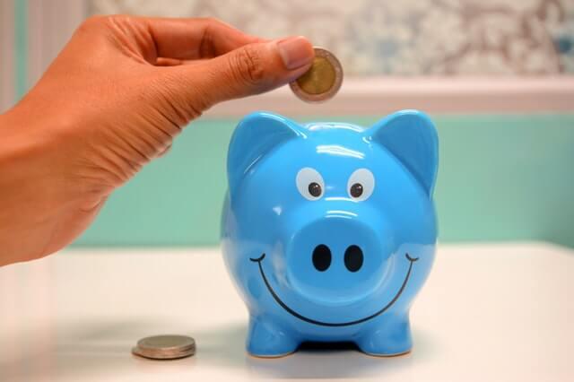 Mutter wirft 2 Euro in ein blaues Sparschwein