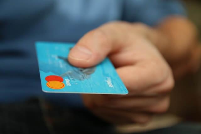 Mann zeigt hellblaue Debitkarte in die Kamera