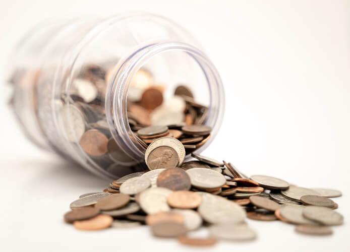Münzgeld liegt dekorativ aus einem liegenden Glas
