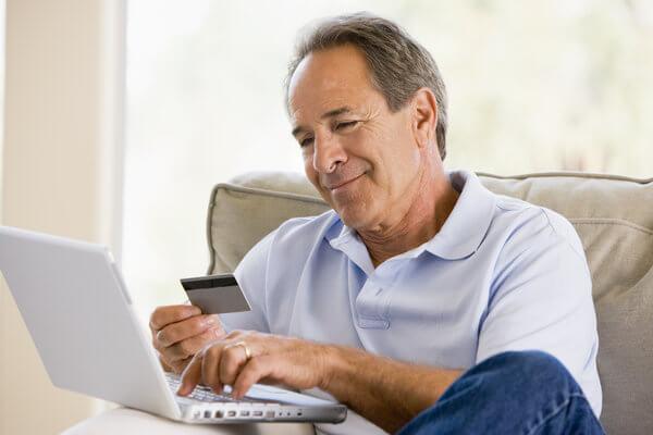Alter Mann sitzt mit einem Laptop auf dem Sofa und schaut auf die Kreditkarte