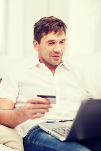 Mann sitzt mit einer Kreditkarte vor dem Laptop