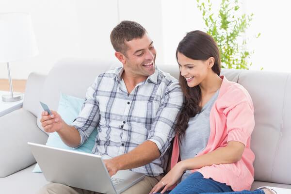 Ehepaar sitzt aufm Sofa und schauen auf dem Laptop