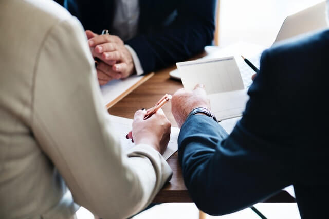 3 Banker sitzen am Tisch und unterzeichnen einen Vertrag