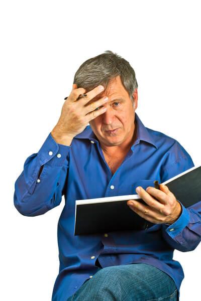 Mann fässt sich aufgrund Bankkonditionen an den Kopf