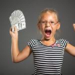 Schülerin hält Geldscheine und freut sich