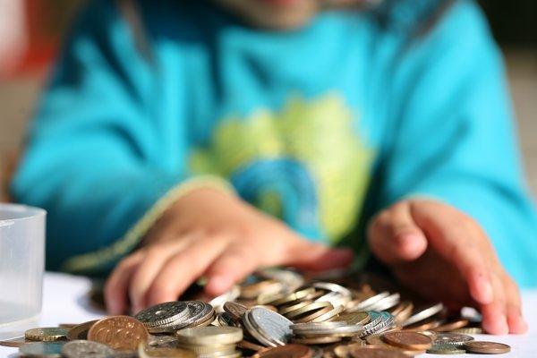 Kind sitzt vor Münzen